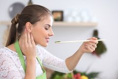 Young woman eating salad by wooden spoon while cooking in a kitchen. Healthy meal, food and kitchen work concept.  Stock Photography