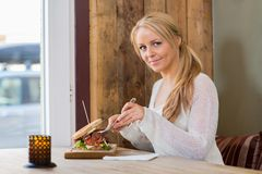 Young Woman Eating Sandwich At Cafe Stock Images