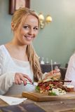 Young Woman Eating Sandwich In Restaurant Stock Photo