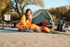 Young woman eating sandwich in sleeping bag near camping tent. Outdoors stock photo