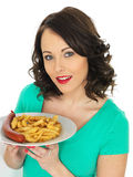 Young Woman Eating Saveloy Sausage and Chips Stock Photography