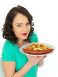 Young Woman Eating Saveloy Sausage and Chips Royalty Free Stock Photography