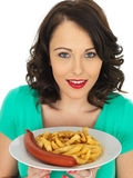 Young Woman Eating Saveloy Sausage and Chips Stock Image