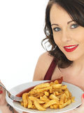 Young Woman Eating Saveloy Sausage with Chips Stock Image