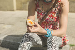 Young woman eating scotch egg in the street Royalty Free Stock Images