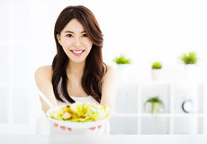 Young woman eating and showing healthy food Stock Photo