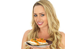 Young Woman Eating Smoked Salmon and Cream Cheese on a Cracker Stock Photo