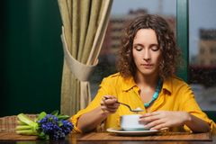 Young woman in yellow shirt eating a soup at restaurant stock photography