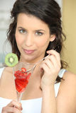 Young woman eating strawberries Royalty Free Stock Images