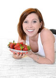 Young  woman eating strawberries on bed Royalty Free Stock Images