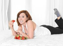 Young  woman eating strawberries on bed Royalty Free Stock Photos