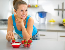 Young woman eating strawberry with yogurt. Happy young woman eating strawberry with yogurt Royalty Free Stock Photo