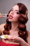 Young woman eating sushi with a chopsticks Stock Photos