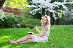Young woman eating sushi in Japanese park Stock Photography