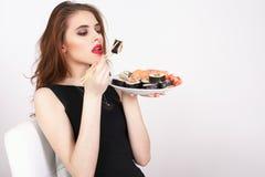 Young woman eating sushi at Japanese restaurant Stock Photos