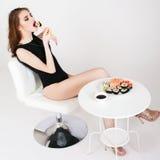 Young woman eating sushi at Japanese restaurant Stock Image