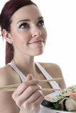 Young woman eating a sushi piece against a white Royalty Free Stock Photography