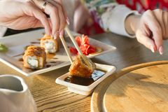 Young woman eating sushi roll in a restaurant royalty free stock photography