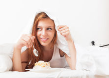 Young woman eating sweet cake under sheet in bed Stock Photos