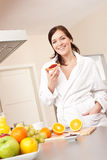 Young woman eating toast for breakfast in kitchen Royalty Free Stock Photography
