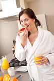 Young woman eating toast for breakfast in kitchen Stock Photo