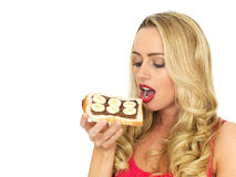Young Woman Eating Toast with Chocolate Spread and Banana Royalty Free Stock Images