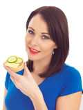 Young Woman Eating Toasted Crumpet with Cheese and Cucumber Royalty Free Stock Photography
