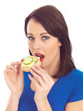 Young Woman Eating Toasted Crumpet with Cheese and Cucumber Royalty Free Stock Photos