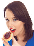 Young Woman Eating Toasted Crumpet and Jam Royalty Free Stock Photography