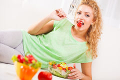 Young woman eating tomato Stock Photography
