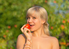 Young woman eating tomato Royalty Free Stock Photography