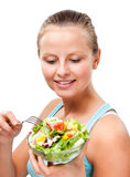 Young woman eating vegetable salad on white background Royalty Free Stock Images