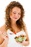 Young woman eating vegetable salad on white background Stock Images