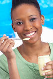 Young Woman Eating Yoghurt In Studio Royalty Free Stock Photography