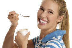 Young woman eating yogurt. On white background Royalty Free Stock Images
