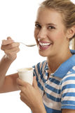 Young woman eating yogurt. On white background Stock Photography