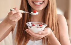 Young woman eating yogurt. Closeup stock photography