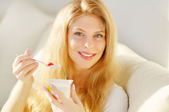 Young woman eating yogurt. At home Royalty Free Stock Image