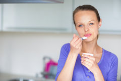 Young woman eating yogurt in kitchen. Happy young woman eating yogurt in kitchen Stock Photography