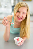 Young woman eating yogurt in kitchen Stock Photos