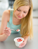 Young woman eating yogurt in kitchen Royalty Free Stock Image