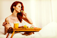Young woman eats breakfast in bed in the morning Stock Images