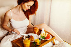 Young woman eats breakfast in bed in the morning Royalty Free Stock Images