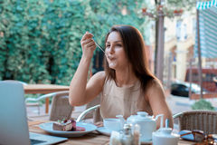 Young woman eats cake royalty free stock photography