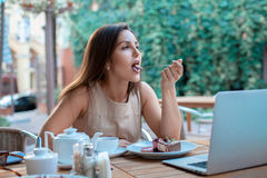Young woman eats delicious cake stock images