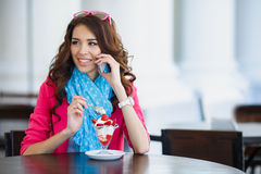 Young woman eats dessert and talking on the phone Royalty Free Stock Photos