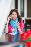 Young woman eats dessert and talking on the phone Stock Photos
