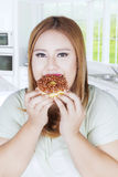 Young woman eats donut Royalty Free Stock Photography