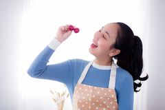Young woman eats fresh grapes in kitchen at home. The young woman eats fresh grapes in kitchen at home Royalty Free Stock Image