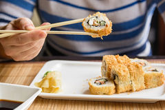 Young woman eats sushi rolls with chopsticks Stock Photo